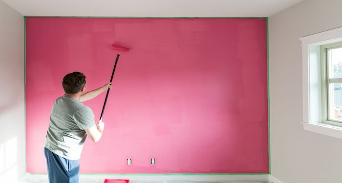 man using roller to paint room wall