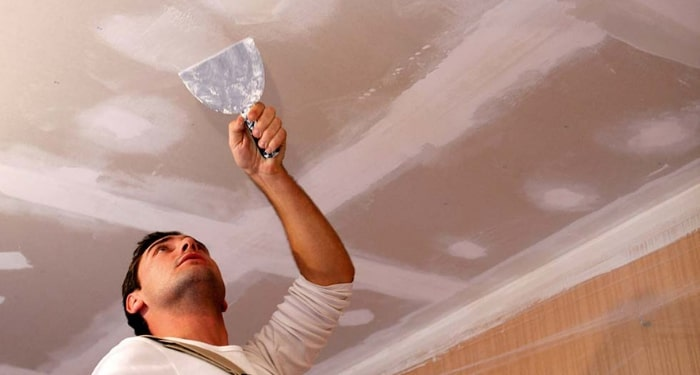 man patching a ceiling