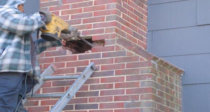 person working on brick chimney
