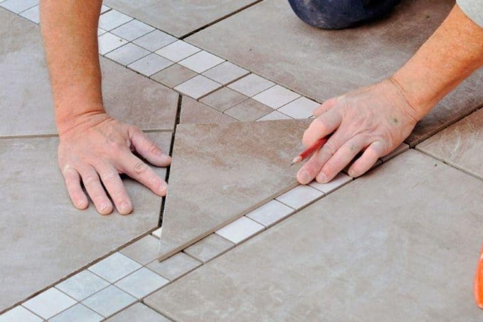 man tiling floor