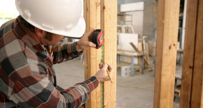 man measuring a door fram
